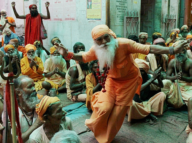 A sadhu dances while others clap ahead of the pilgrimage