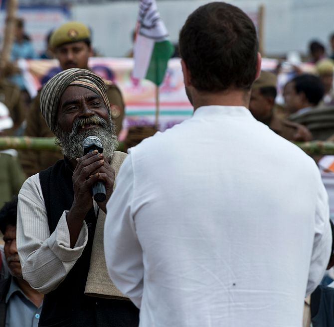 A rickshaw-puller interacts with Rahul Gandhi outside the Cantonment Railway Station in Varanasi