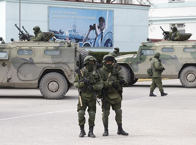 Armed servicemen wait near Russian army vehicles outside a Ukranian border guard post in the Crimean town of Balaclava