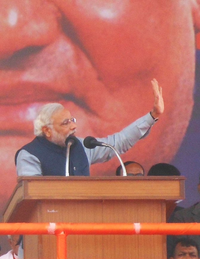 BJP PM nominee waves to supporters as he addresses a rally in Lucknow