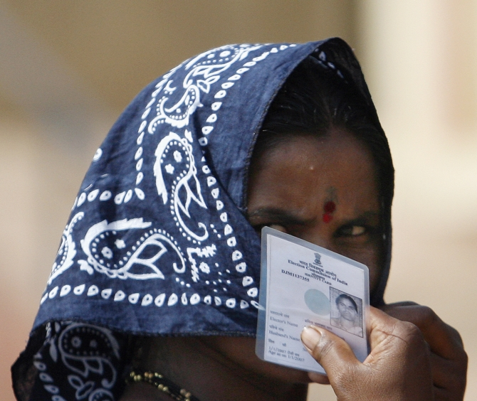 A woman holds her voting card near Mumbai
