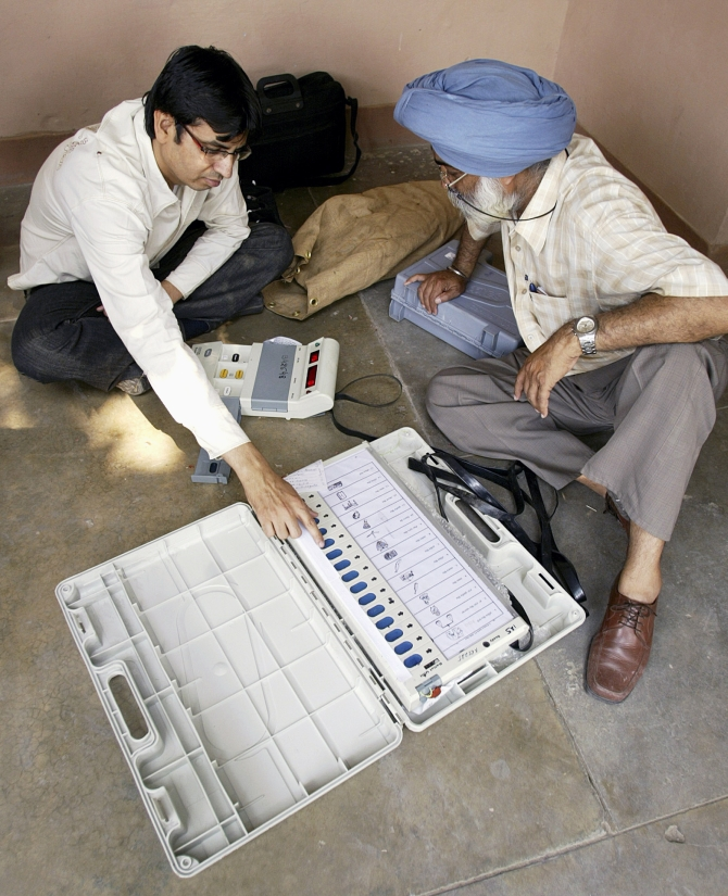 Polling officers check an EVM at a distribution centre in Amritsar