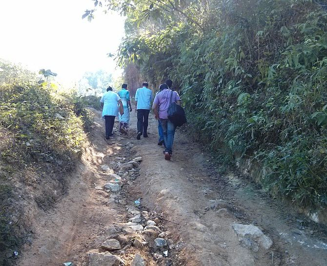 Dr M R Rajagopal and his team walk up an unpaved path to a patient's home.
