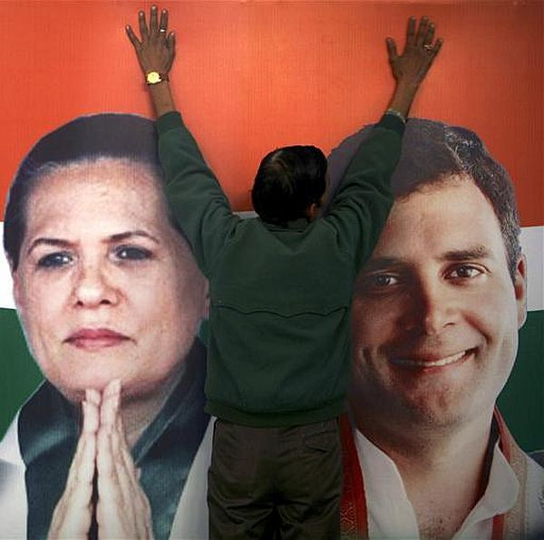 A worker installs a hoarding containing pictures of Congress president Sonia Gandhi and Rahul Gandhi at the party's headquarters in Jammu