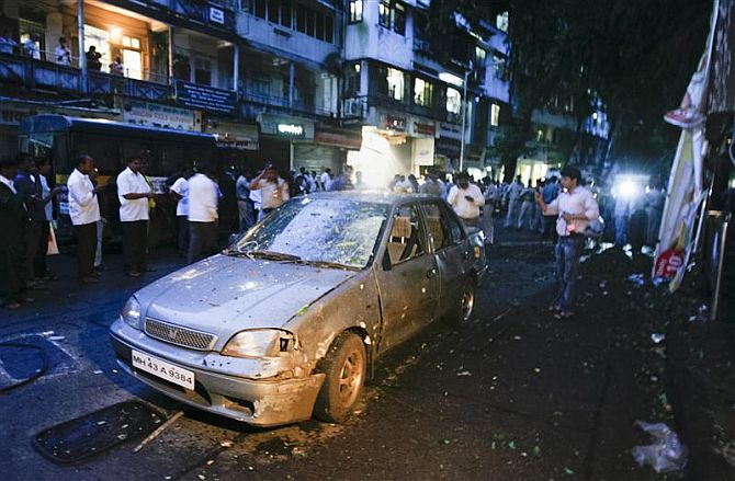 A car is seen damaged at the site of a bomb explosion in the Dadar area of Mumbai July 13, 2011.