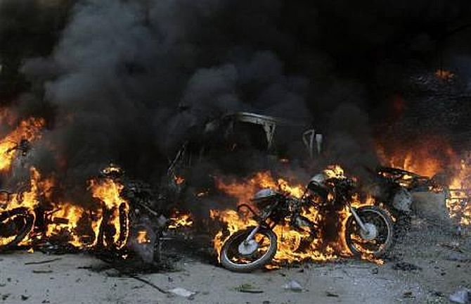 Damaged vehicles burn after a bomb blast in Guwahati in this October 30, 2008 file photo