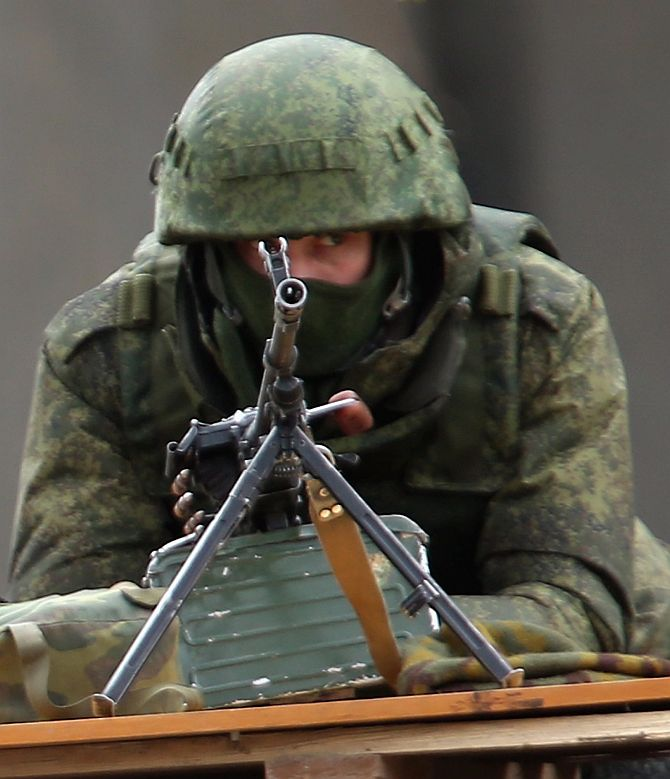 A soldier without identifying insignia mans a machine gun outside the Crimean parliament building shortly after several dozen soldiers took up positions