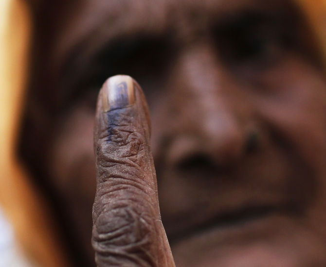 A woman shows her ink-marked finger after casting her vote at a polling station during the state assembly election in this photograph