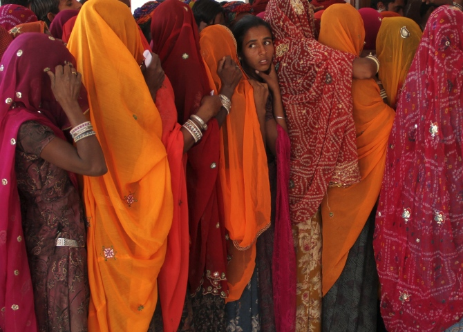 Women line up in a queue outside a polling booth to cast their vote during the state assembly election in Birchiwayas village in Ajmer.