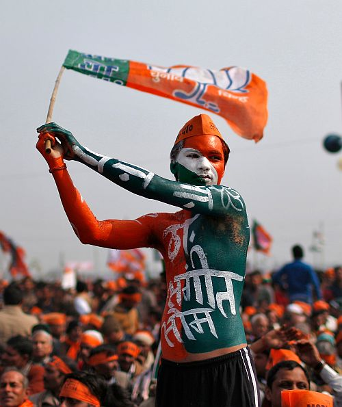 A BJP supporter waves the party's flag during Narendra Modi's rally in Uttar Pradesh