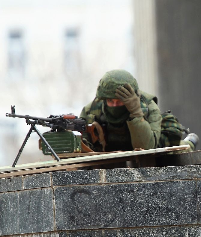 Soldiers without identifying insignia man machine guns outside the Crimean parliament building in Simferopol, Ukraine.