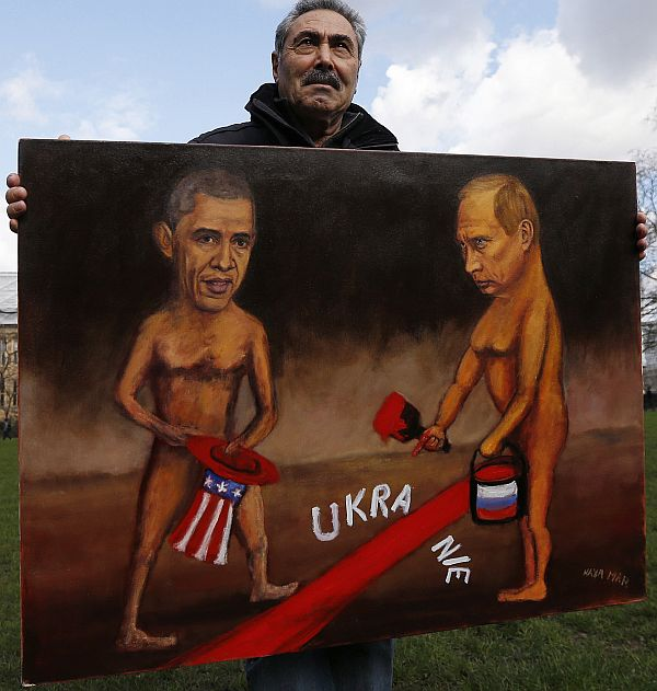 Artist Kaya Mar holds a satirical painting depicting US President Barack Obama and Russia's President Vladimir Putin in Ukraine.
