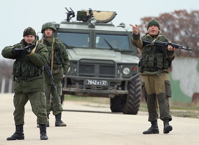 Troops under Russian command, before firing weapons into the air at an approaching group of over 100 unarmed Ukrainian troops at the Belbek airbase, which the Russian troops are occcupying, in Crimea.