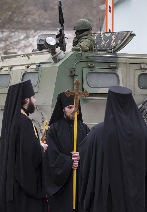Orthodox monks besides a soldier in a Russian army vehicle in the Crimean town of Balaclava.