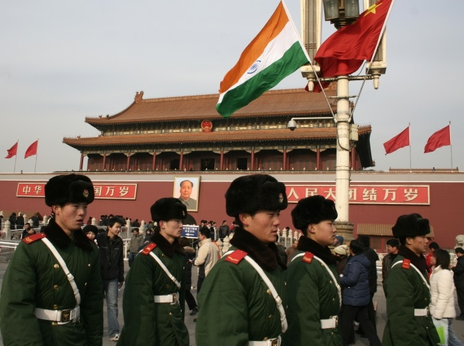 Chinese paramilitary policemen walk past an Indian flag in front of Tiananmen Gate in Beijing
