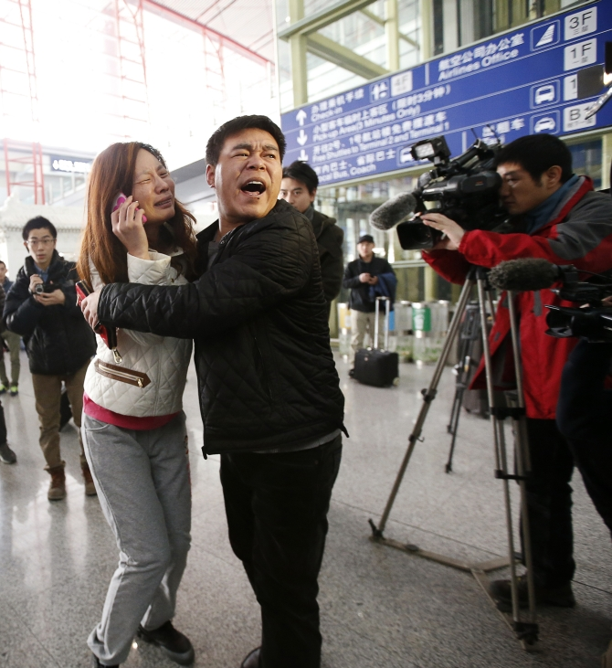 A relative of a passenger onboard Malaysia Airlines flight MH370 cries as she talks on her mobile phone