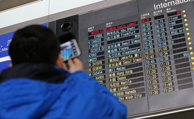 A man takes pictures of a flight information board displaying the Scheduled Time of Arrival of Malaysia Airlines flight MH370 (top, in red) at the Beijing Capital International Airport