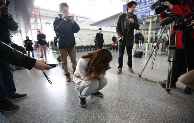 Journalists attempt to interview a woman who is the relative of a passenger on Malaysia Airlines flight MH370