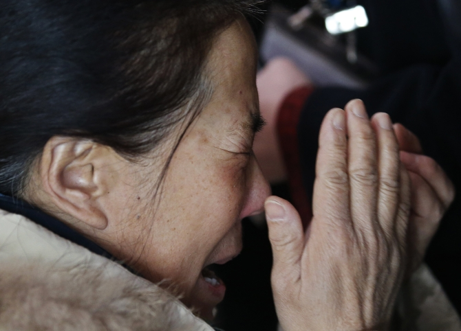 A relative of a passenger onboard Malaysia Airlines flight MH370 cries, surrounded by journalists, at the Beijing Capital International Airport in Beijing
