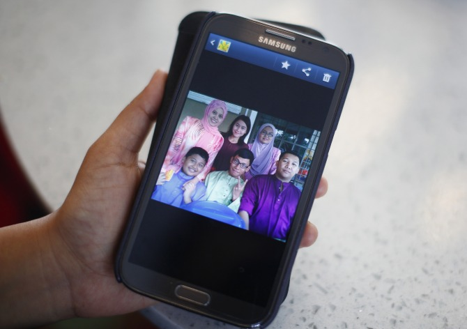 Arni Marlina, 36, a family member of a passenger onboard the missing Malaysia Airlines flight MH370, shows a family picture on her mobile phone, at a hotel in Putrajaya.