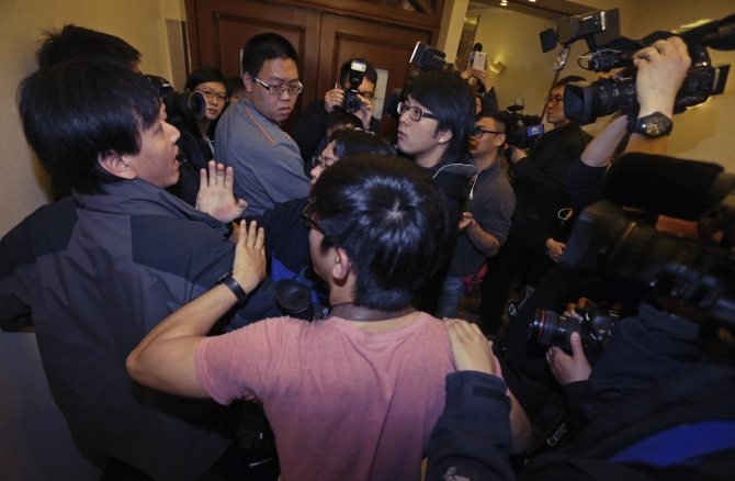A journalist (left) scuffles with another (centre, with glasses) as they wait for relatives of passengers of Malaysia Airlines flight MH370 at a hotel in Beijing.