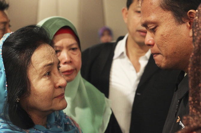 Rosmah Mansor (left), wife of Malaysian Prime Minister Najib Razak, cries with family members of passengers on the missing Malaysia Airlines flight MH370, at a hotel in Putrajaya