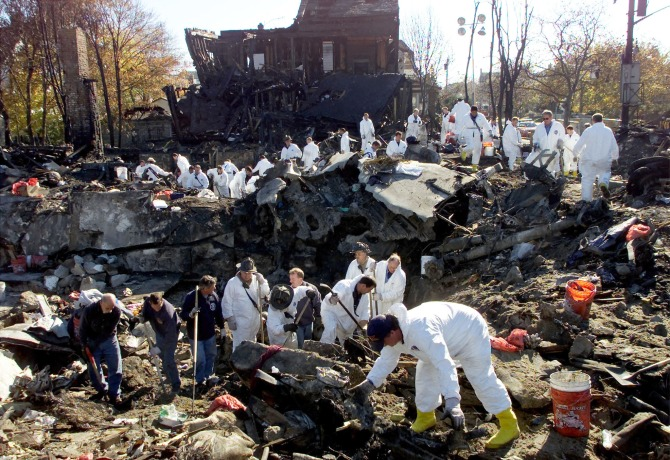 New York City firefighters in protective gear search the pit at the corner of Beach 131st street and Newport Street in the Rockaway Beach section of Queens, New York for human remains and evidence from the crash of American Airlines flight 587.