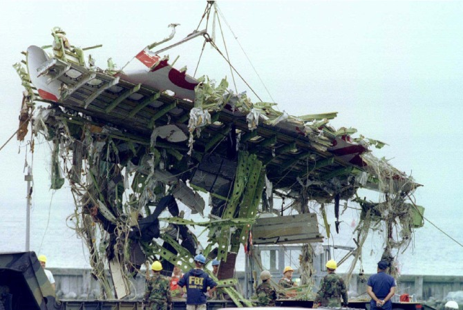 A large section of fuselage from TWA Flight 800 is lifted to shore from a navy barge August 3 at the Shinnecock Coast Guard station.