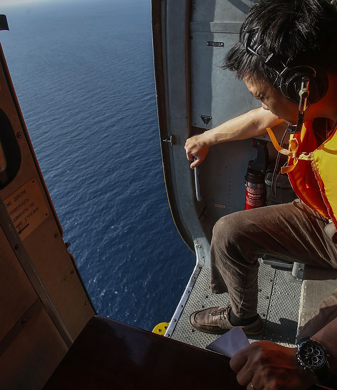 An officer looks out of a helicopter during a mission to find the Malaysia Airlines flight MH370 that disappeared from radar screens in the early hours of Saturday, near Tho Chu island