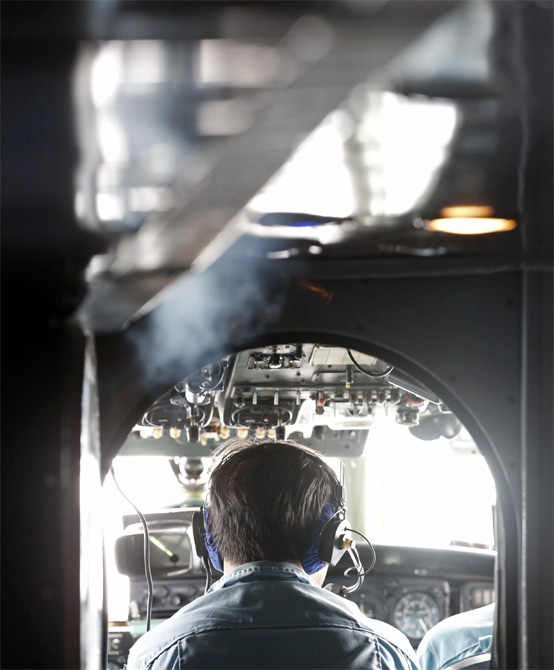 A military personnel works on board a Vietnamese airforce AN-26 during a mission to find missing Malaysia Airlines flight