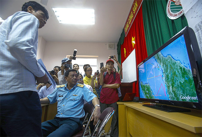 Deputy commander of Vietnam Air Force Do Minh Tuan looks at a map on a TV screen during a news conference about their mission