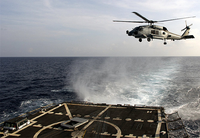 A US Navy SH-60R Seahawk helicopter takes off from the destroyer 'USS Pinckney' in the Gulf of Thailand, to assist in the search