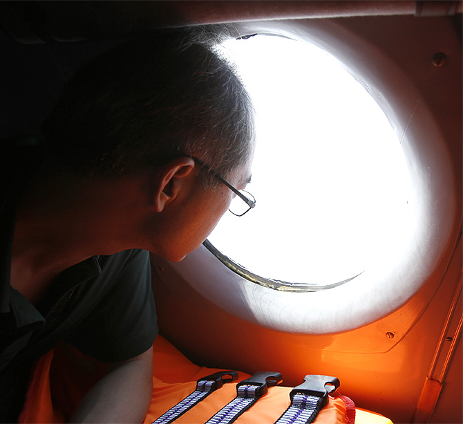 A Chinese journalist looks out from the window of a Vietnamese airforce AN-26 during a mission to find the missing Malaysia Airlines flight