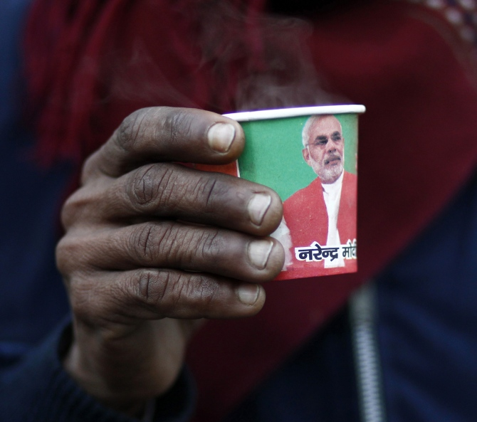 A man holds a paper cup carrying a portrait of at a tea stall in the old quarters of Delhi.