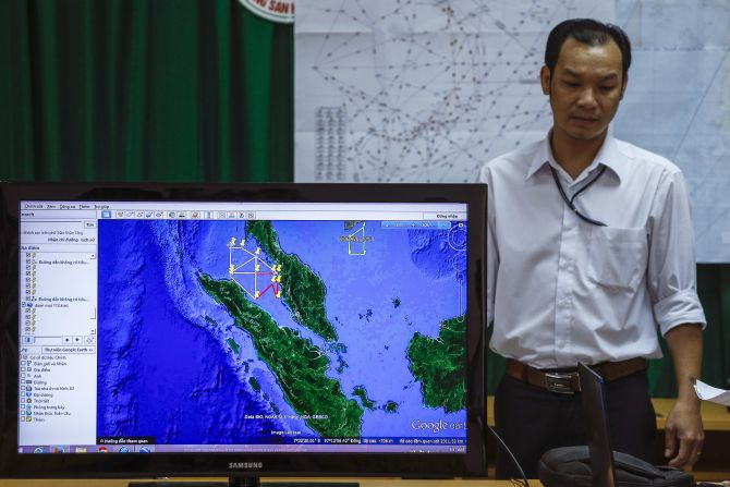 A Vietnamese officer stands next to a TV screen showing a flight route during a news conference about their mission to find missing Malaysia Airlines flight