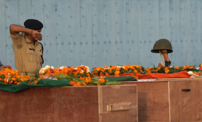 Central Reserve Police Force policeman pays his last respecst near the coffins of policemen who died in a maoist attack in Chattisgarh