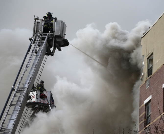 Firefighters try to extinguish a fire at the site of a building collapse in Harlem, New York