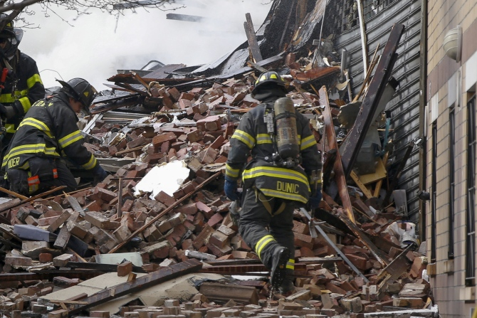 Firefighters go through debris and rubble at the site of a building collapse and fire in Harlem, New York