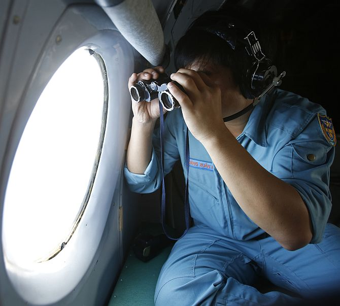 Military officer Dang Xuan Hung looks out a window of a Vietnam Air Force aircraft AN-26 during a mission to find the missi