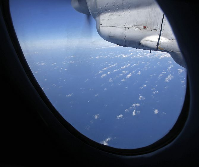 Clouds hover outside the window of a Vietnam Air Force aircraft AN-26 during a mission to find the missing Malaysia Airlines flight MH370