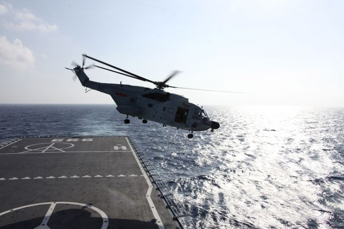 A Chinese helicopter takes off from a warship to search the waters suspected to be the site of the missing flight MH370