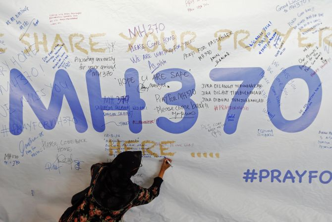 A woman writes a message of support and hope for the passengers of the missing MH370 on a banner at the Kuala Lumpur International Airport
