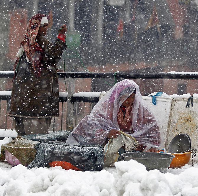 A Kashmiri fisherwoman arranges containers with fish as she waits for customers during heavy snowfall in Srinagar