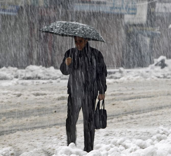 A man holds an umbrella as he walks on a road during heavy snowfall in Srinagar