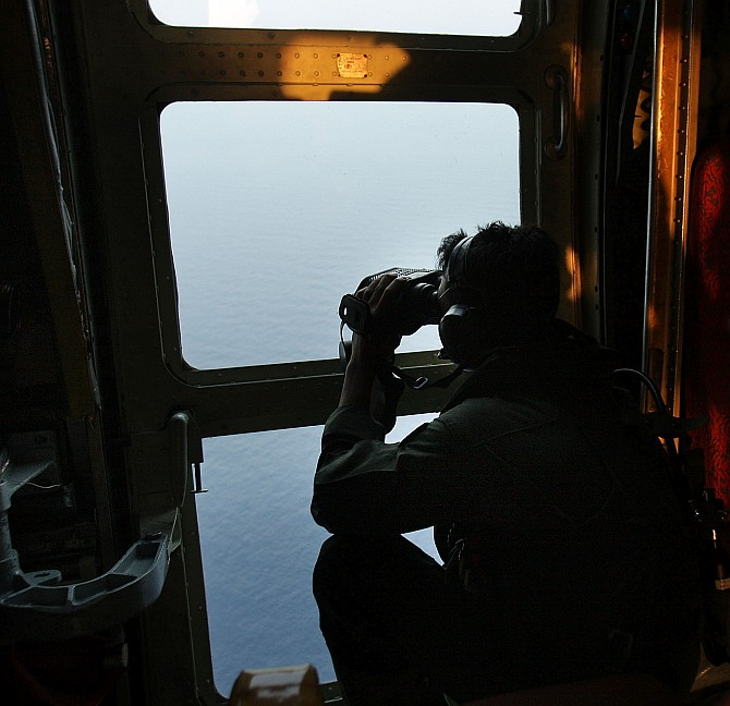 Sgt Zulhelmi Hassan of the Malaysian Air Forces searches the water for signs of debris from the Malaysian airliner during a search and rescue mission flight