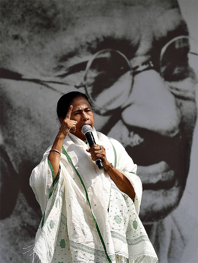 West Bengal CM addresses her supporters in front of a portrait of Mahatma Gandhi during a rally ahead of the 2014 general elections, in New Delhi March