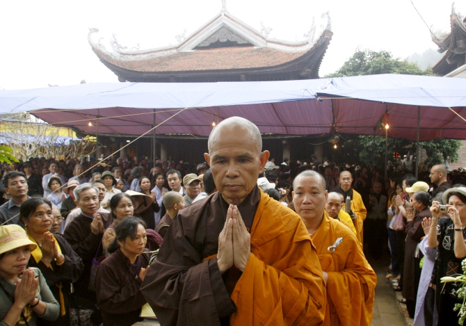 Buddhist monk Thich Nhat Hanh (centre), walks among believers after finishing a speech at the opening ceremony of a requiem mass at the Non Nuoc pagoda in Soc Son mountain, 64 km of Hanoi.