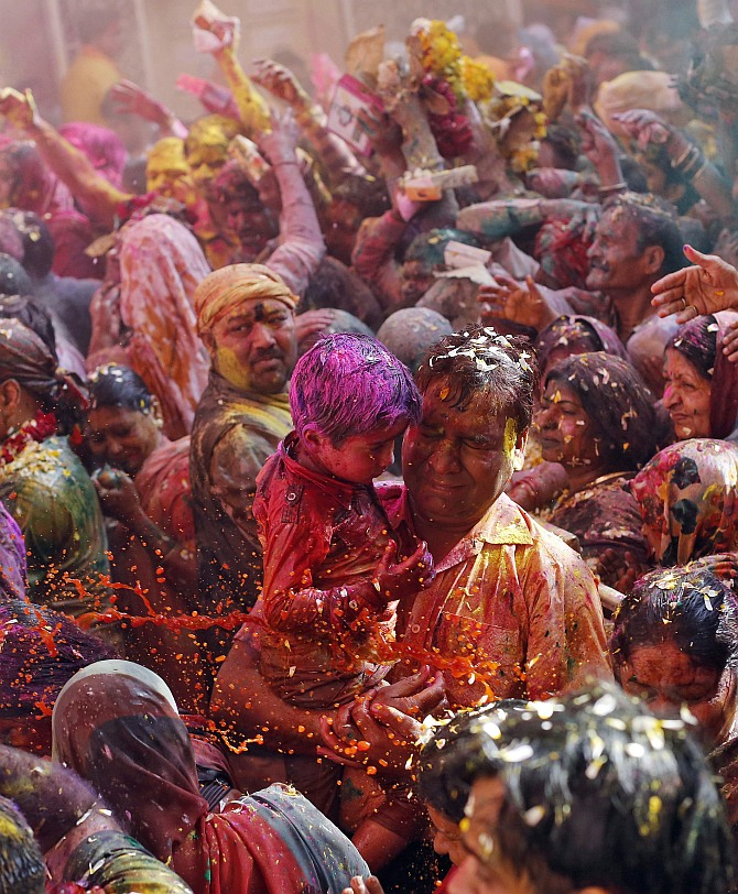 Devotees react as priests (unseen) throw coloured water on them during Holi celebrations at the Bankey Bihari temple in Vrindavan, in Uttar Pradesh