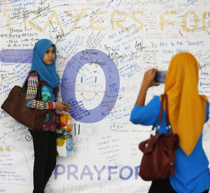 A girl has her picture taken after leaving messages of support and hope for the passengers of the missing Malaysia Airlines MH370 at the Kuala Lumpur International Airport