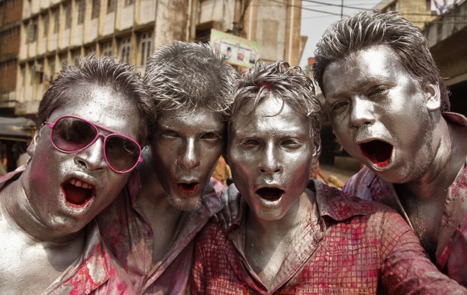 People daubed in colours dance as they celebrate Holi in Guwahati.